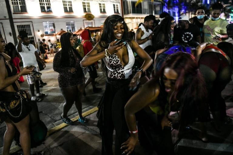 People dance on Ocean Drive in Miami Beach, on March 17, 2021