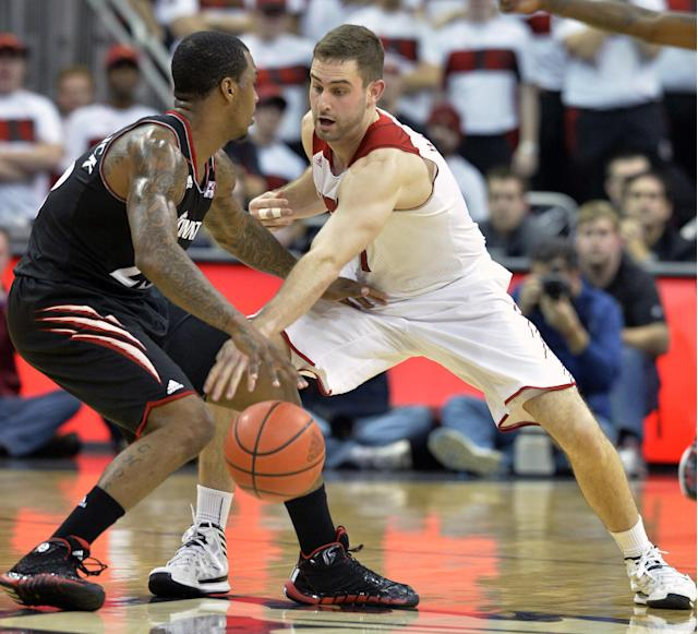 Louisville's Luke Hancock, right, tries to knock the ball away from Cincinnati's Sean Kilpatrick during the second half of an NCAA college basketball game Thursday, Jan. 30, 2014, in Louisville, Ky. Cincinnati defeated Louisville 69-66. (AP Photo/Timothy D. Easley)