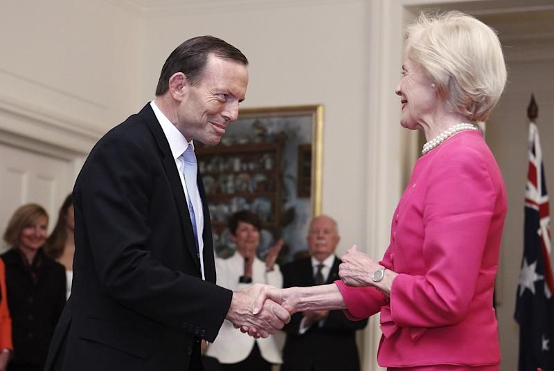 Tony Abbott, left, shakes hands with Governor General Quentin Bryce after being sworn in as the 28th prime minister of Australia at Government House in Canberra Wednesday, Sept. 18, 2013. Abbott promised immediate action to slow the stream of asylum seekers arriving by boats from Indonesia and to repeal an unpopular carbon tax levied by the previous administration. (AP Photo/Stefan Postles, Pool)
