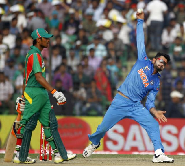India's captain Virat Kohli bowls as Bangladesh's Anamul Haque (L) watches during their Asia Cup 2014 one-day international (ODI) cricket match in Fatullah February 26, 2014. REUTERS/Andrew Biraj (BANGLADESH - Tags: SPORT CRICKET)
