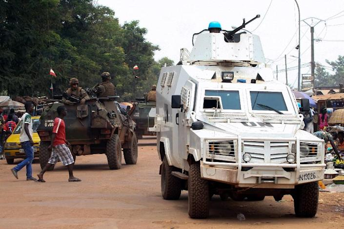 Officers from the UN mission in the Central African Republic (MINUSCA) patrol a market in Bangui on September 14, 2015 as patrol vehicles from the French Operation Sangaris forces drive past (AFP Photo/Edouard Dropsy)