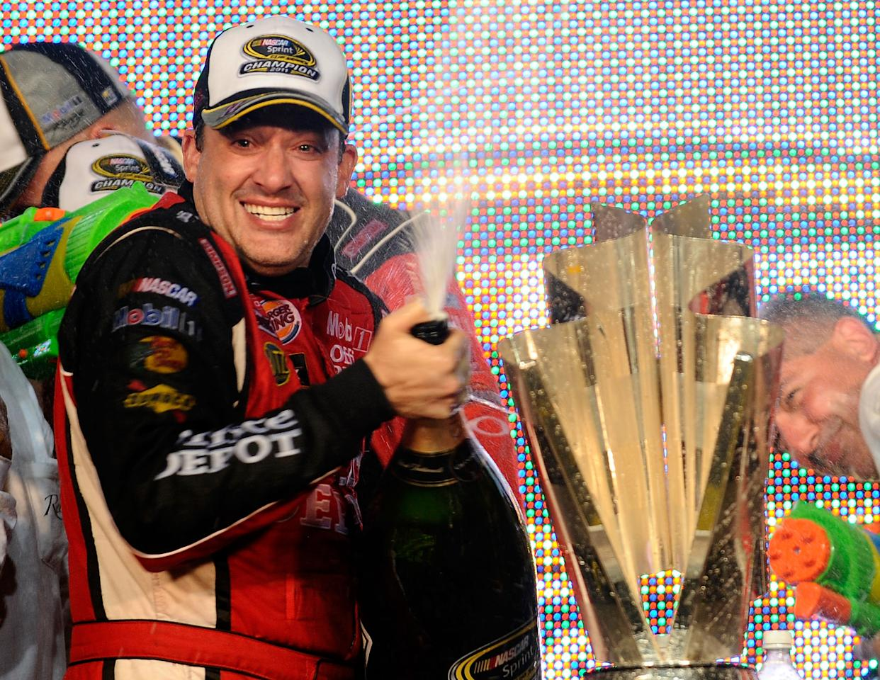 HOMESTEAD, FL - NOVEMBER 20:  Tony Stewart, driver of the #14 Office Depot/Mobil 1 Chevrolet, celebrates with the trophy in Victory Lane after winning the NASCAR Sprint Cup Series Ford 400 and the 2011 Series Championship at Homestead-Miami Speedway on November 20, 2011 in Homestead, Florida. Stewart wins his third NASCAR Championship.  (Photo by Jared C. Tilton/Getty Images)