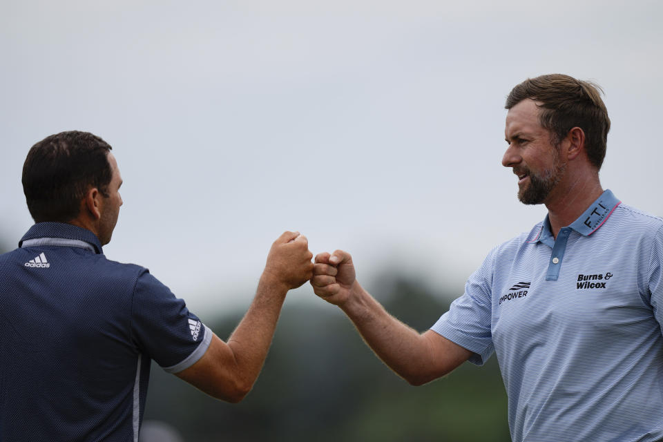 Webb Simpson, right, bumps fists with Sergio Garcia, of Spain, on the 18th hole during the second round of the Masters golf tournament on Friday, April 9, 2021, in Augusta, Ga. (AP Photo/David J. Phillip)