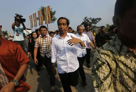 """Indonesian presidential candidate Joko """"Jokowi"""" Widodo (C) walks while waiting for the results announcement by the Elections Commission, at Waduk Pluit in Jakarta July 22, 2014. REUTERS/Beawiharta"""
