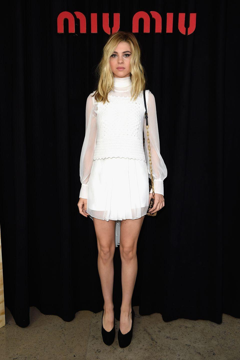<p>The star attended Paris Fashion Week to watch the Miu Miu SS14 show in a white, high-neck midi dress with sheer sleeves, teamed with a pair of black heels. </p>