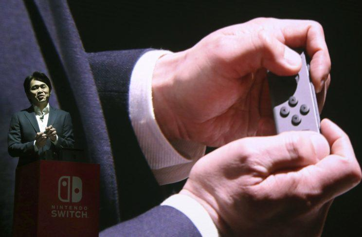 Nintendo Switch General Producer Yoshiaki Koizumi shows how the Joy-Con controller works at the launch event in Japan