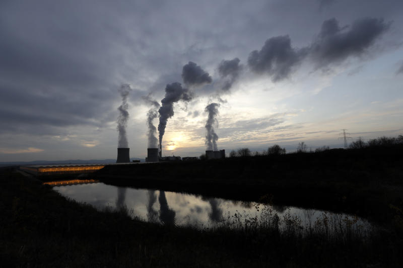 Smoke rises from chimneys of the Turow power plant located by the Turow lignite coal mine near the town of Bogatynia, Poland, Tuesday, Nov. 19, 2019. The Turow lignite coal mine in Poland has an impact on the environment and communities near the border of three neighboring countries, the Czech Republic, Germany and Poland. Plans to further expand the huge open pit mine have caused alarm among residents who fear things might get even worse. (AP Photo/Petr David Josek)