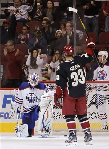 Phoenix Coyotes' Adrian Aucoin (33) celebrates a goal by teammate Lauri Korpikoski as Edmonton Oilers' Devan Dubnyk, left, kneels on the ice in the first period in an NHL hockey game Thursday, Dec. 15, 2011, in Glendale, Ariz.(AP Photo/Ross D. Franklin)