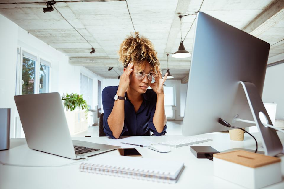 Female financial expert sitting with head in hands at desk. Tired businesswoman is staring at computer monitor in office. She is having headache.