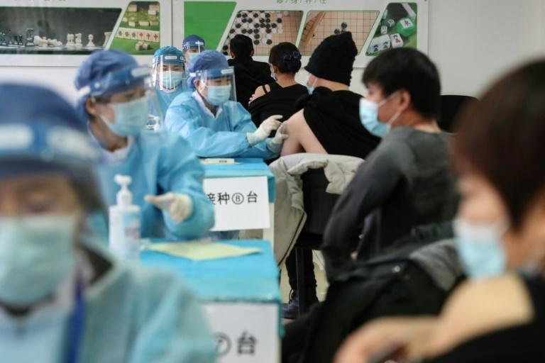 People receive vaccines against the Covid-19 coronavirus at a temporary vaccination centre in Beijing