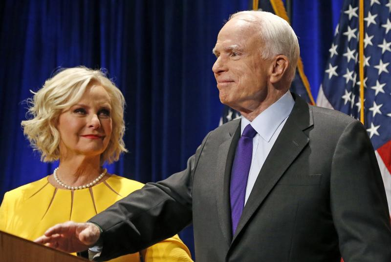 """FILE - In this Tuesday, Nov. 8, 2016, file photo, Sen. John McCain, R-Ariz., right, pauses as his wife, Cindy McCain, looks at him on stage after giving his victory speech as he announces his win over Democratic challenger Rep. Ann Kirkpatrick, in Phoenix. The family of the late Sen. John McCain says they want to build a library on land donated by Arizona State University to house his archives and provide a """"gathering place"""" for respectful dialogue. (AP Photo/Ross D. Franklin, File)"""