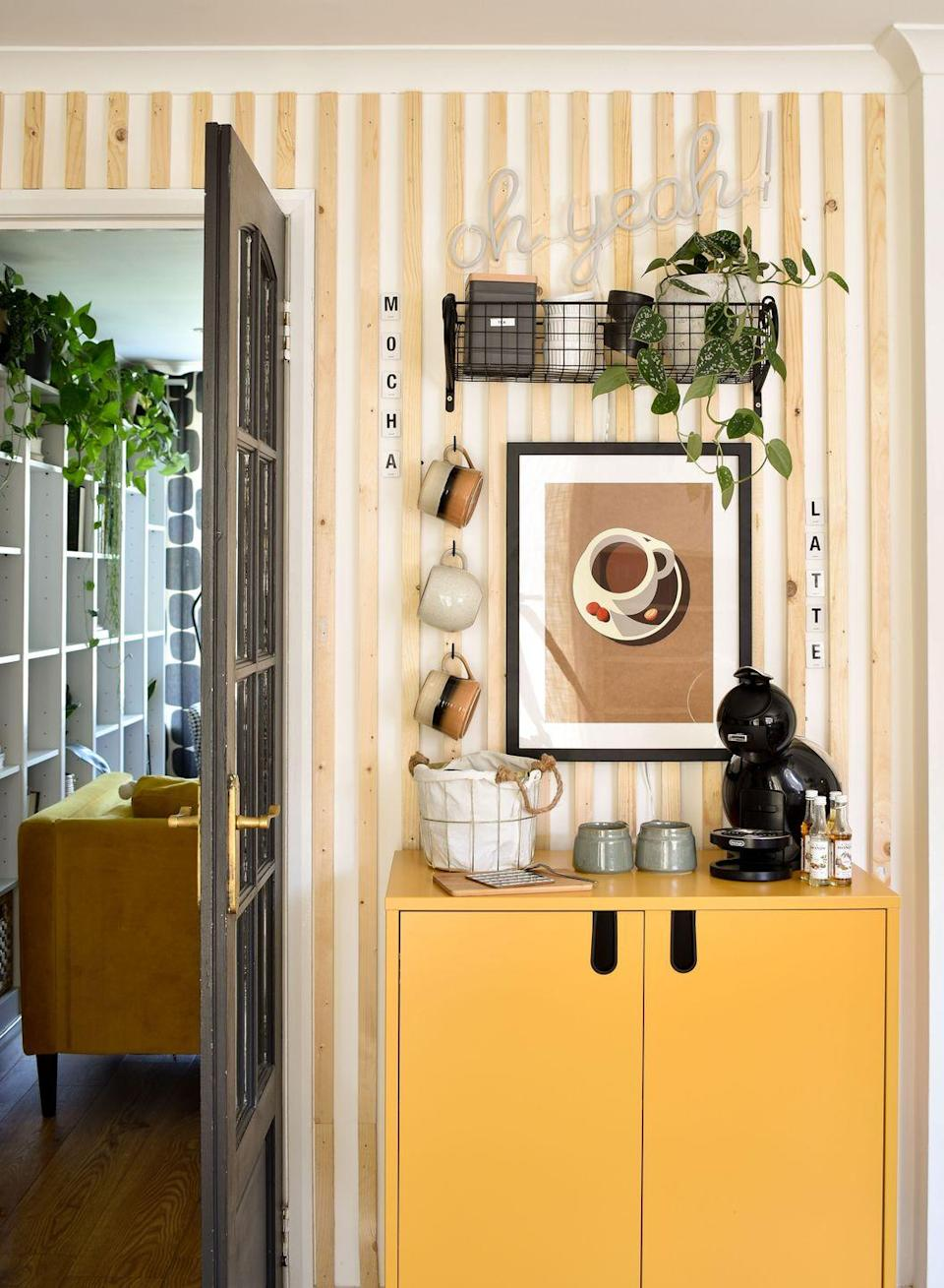 """<p>""""My husband and I are big coffee drinkers, so it made sense to have a dedicated space for to store our coffee. The feature wall behind is made from raw wood planks and really helps to frame the space. The prettier items are displayed on the hooks and shelf and the other accessories are in the cabinet. The <a href=""""https://go.redirectingat.com?id=127X1599956&url=https%3A%2F%2Fwww.wayfair.co.uk%2FTenzo--Uno-2-Door-Storage-Cabinet-8552-L102-K%7EXKD1305.html%3Fcjevent%3Dd31cb7b375c811eb804a004c0a180514%26refID%3DCJUK4653527%26PID%3D7947610&sref=https%3A%2F%2Fwww.harpersbazaar.com%2Fuk%2Fculture%2Flifestyle_homes%2Fg35595137%2Finside-the-home-of-interiors-blogger-medina-grillo%2F"""" rel=""""nofollow noopener"""" target=""""_blank"""" data-ylk=""""slk:cabinet is from Wayfair,"""" class=""""link rapid-noclick-resp"""">cabinet is from Wayfair, </a>and the shelf is from <a href=""""https://go.redirectingat.com?id=127X1599956&url=https%3A%2F%2Fwww.notonthehighstreet.com%2F&sref=https%3A%2F%2Fwww.harpersbazaar.com%2Fuk%2Fculture%2Flifestyle_homes%2Fg35595137%2Finside-the-home-of-interiors-blogger-medina-grillo%2F"""" rel=""""nofollow noopener"""" target=""""_blank"""" data-ylk=""""slk:Not On The High Street"""" class=""""link rapid-noclick-resp"""">Not On The High Street</a>.</p>"""