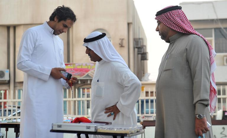 A Saudi street vendor speaks with a customer in the mainly Shiite town of Qatif, November 11, 2014. Solidarity gestures by Sunni leaders are helping to bridge a divide with the minority