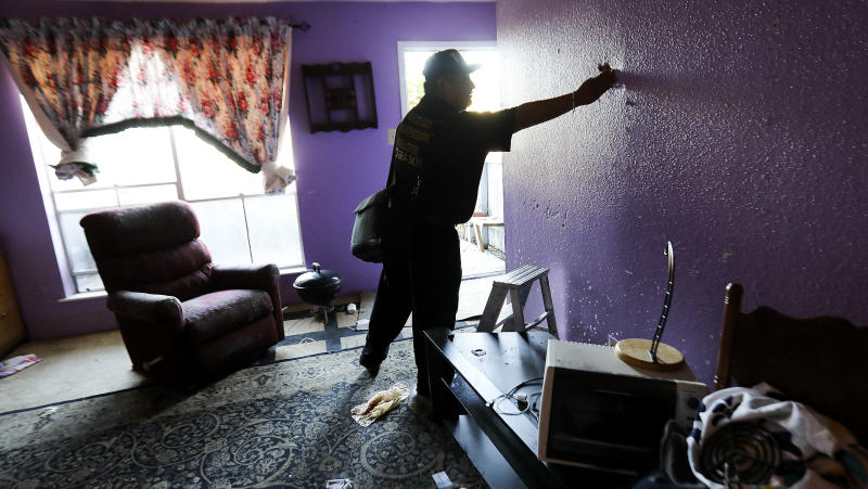 Community organizer Alain Cisneros easily puts his hand through a soaked wall in a Rockport Apartment that was damaged by Tropical Storm Harvey on Thursday, Sept. 7, 2017, in Houston.