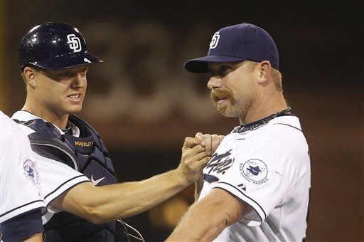 San Diego Padres catcher Nick Hundley pounds the chest of pitcher Dale Thayer after Thayer earned the save in the Padres 3-2 victory over the Colorado Rockies in a baseball game Monday, May 7, 2012 in San Diego. (AP Photo/Lenny Ignelzi)