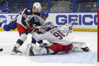 Columbus Blue Jackets goaltender Elvis Merzlikins (90) makes a save against Tampa Bay Lightning's Barclay Goodrow (19) as Dean Kukan (46) defends during the second period of an NHL hockey game Thursday, April 22, 2021, in Tampa, Fla. (AP Photo/Mike Carlson)