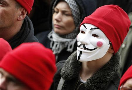 "A protester wearing a red cap, the symbol of protest in Brittany, and a Guy Fawkes mask takes part in a demonstration to maintain jobs in the region and against an ""ecotax"" on commercial trucks, in Carhaix, western France, November 30, 2013. REUTERS/Mal Langsdon"