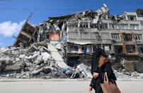 A Palestinian woman walks past a destroyed building in the Al-Rimal district of Gaza City as residents took stock of the damage caused during Israeli bombardment a day after a ceasefire took effect