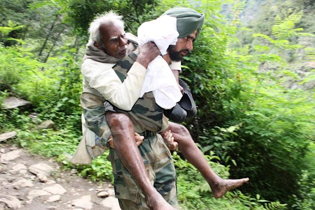 "In this handout photograph released by the Indian Ministry of Defence, Indian military personnel help rescue pilgrims that were stranded by flood waters in Uttarakhand state, on June 22, 2013. Relief teams were racing against time June 22 to rescue tens of thousands of stranded people in rain-ravaged northern India as the death toll from flash floods and landslides neared 600. Floods and landslides from monsoon rains have also struck neighbouring Nepal, leaving at least 39 people dead, the Nepalese government said. AFP PHOTO/MINISTRY OF DEFENCE ----EDITORS NOTE---- RESTRICTED TO EDITORIAL USE - MANDATORY CREDIT - ""AFP PHOTO/MINISTRY OF DEFENCE"" - NO MARKETING NO ADVERTISING CAMPAIGNS - DISTRIBUTED AS A SERVICE TO CLIENTS -----"
