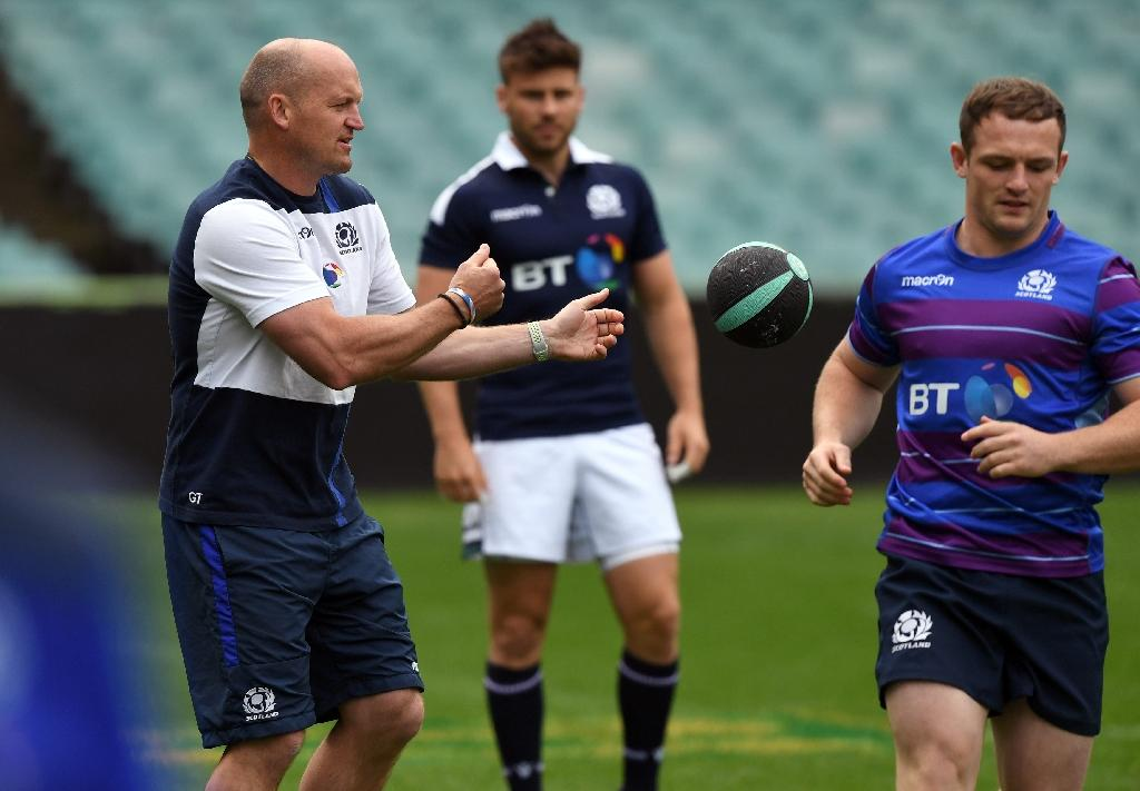 Scotland rugby coach Gregor Townsend (L) passes the ball during their Captain's Run in Sydney on June 16, 2017.Scotland plays Australia in a Test match in Sydney on June 17. (AFP Photo/WILLIAM WEST)
