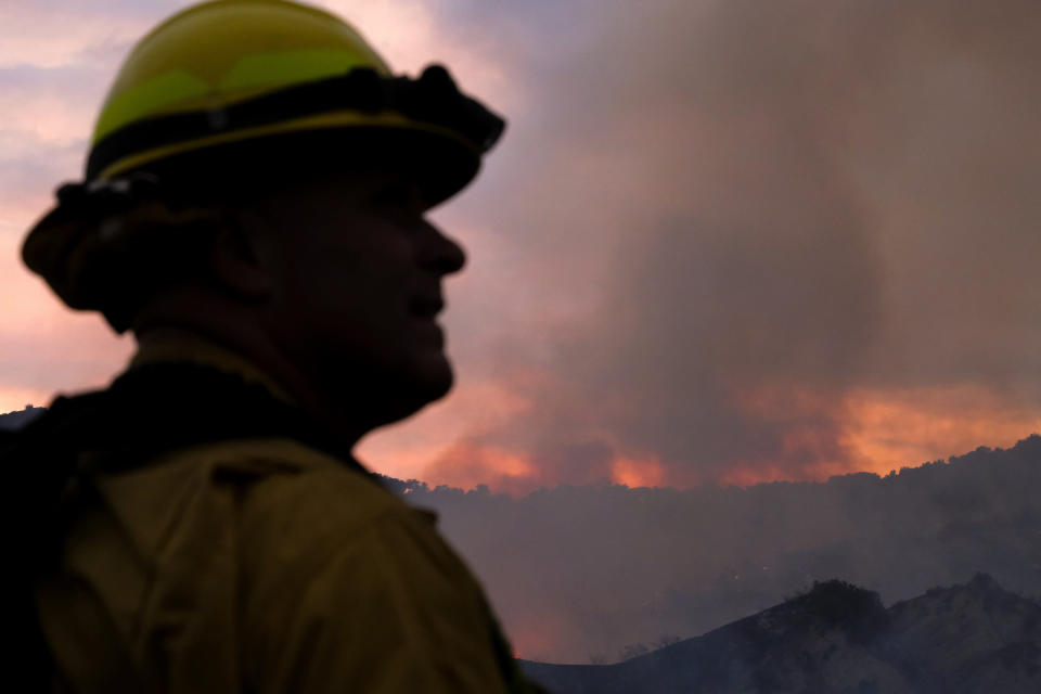 A firefighter keeps watch as smoke rises from a brush fire scorching at least 100 acres in the Pacific Palisades area of Los Angeles on Saturday, May 15, 2021. (AP Photo/Ringo H.W. Chiu)