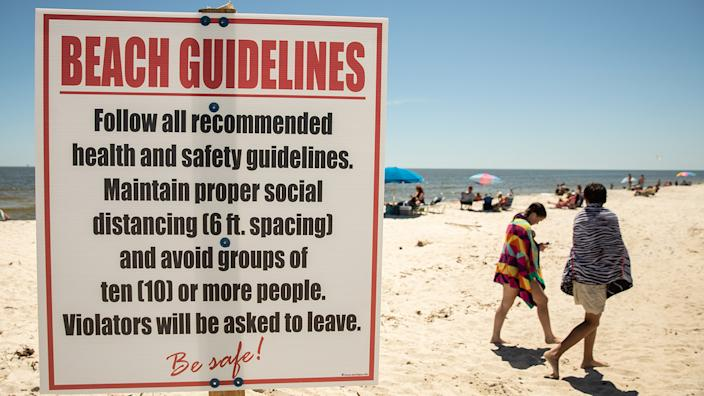"""A guidelines sign at a public beach includes """"maintain proper social distance"""" and """"avoid groups of 10 or more people"""""""