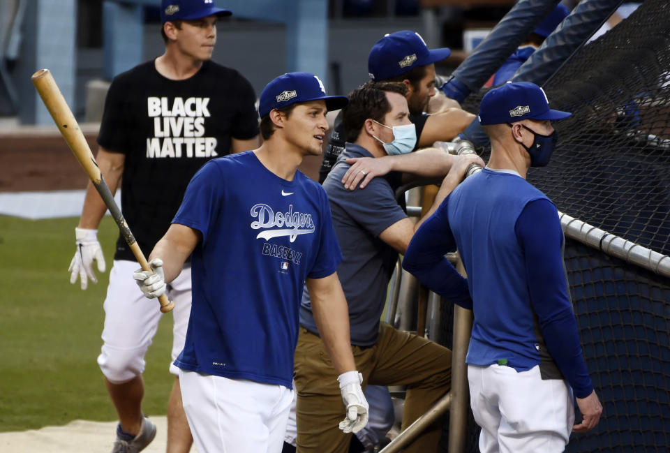Los Angeles Dodgers' Corey Seager, left, looks on during batting practice, Tuesday, Sept. 29, 2020, at Dodger Stadium in Los Angeles, ahead of Wednesday's Game 1 of a National League wild-card baseball series against the Milwaukee Brewers. (AP Photo/Chris Pizzello)