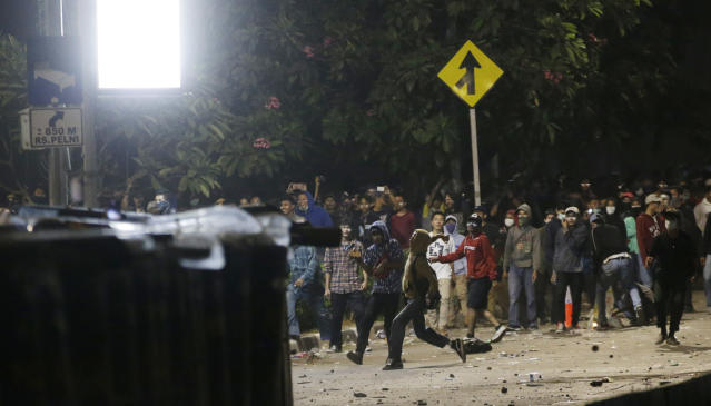 Student protesters throw stones to riot police during a protest outside the parliament in Jakarta, Indonesia Tuesday, Sept. 24, 2019. Police fired tear gas and water cannons Tuesday to disperse thousands of rock-throwing students protesting a new law that they said has crippled Indonesia's anti-corruption agency.(AP Photo/Achmad Ibrahim)
