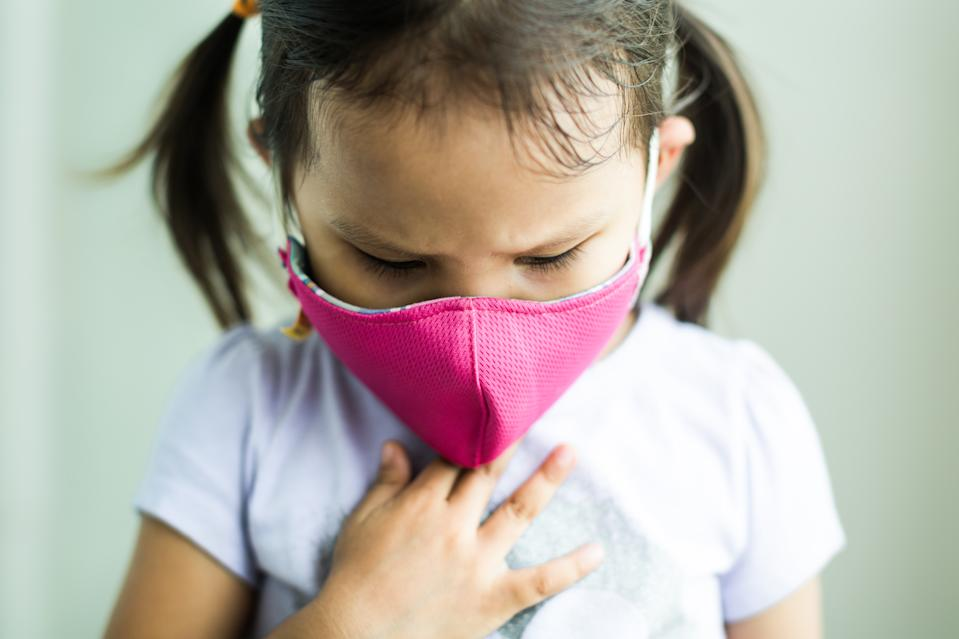 Little asian girl suffering from dirty air pollution, holding her chest wearing a protective mask outside.