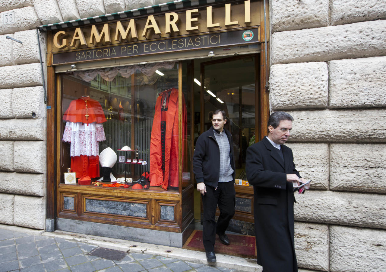 "Two priests exit the Gammarelli clergy clothing shop, downtown Rome, Thursday, Feb. 6, 2014. The Gammarelli family has been dressing Roman Catholic clergy since 1793. Sixth generation Lorenzo Gammarelli said Francis' call for sobriety _ which Esquire credited with subtly signaling ""a new era (and for many, renewed hope) for the Catholic Church"" _ hadn't really affected business at all. ""Those who were simple before remain simple today,"" he said. And vice versa. ""Simplicity is not here."" (AP Photo/Andrew Medichini)"