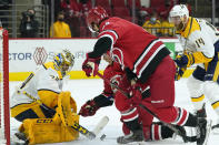 Carolina Hurricanes center Martin Necas (88) and right-wing Jesper Fast (71) try to score against Nashville Predators goaltender Juuse Saros (74) while defenseman Mattias Ekholm (14) looks on at right during the second period of an NHL hockey game in Raleigh, N.C., Saturday, April 17, 2021. (AP Photo/Gerry Broome)