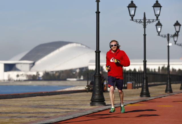 A man jogs along a coastline during a sunny day as the Olympic Park is seen on background during the 2014 Winter Olympic Games in Sochi February 12, 2014. REUTERS/Shamil Zhumatov (RUSSIA - Tags: SPORT OLYMPICS ENVIRONMENT)