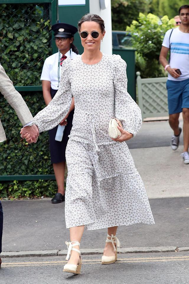 "<p>In a printed long sleeve Anna Mason London dress, lace-up cream <a rel=""nofollow"" href=""https://www.net-a-porter.com/us/en/product/1035916"">espadrilles by Castañer</a>, Ray-Ban sunglasses, and a basket clutch while attending Wimbledon with her husband, James Matthews.</p>"