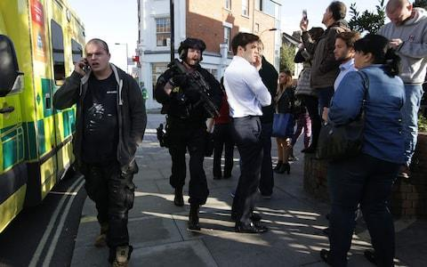 <span>An armed police officer moves through pedestrians at Parsons Green</span> <span>Credit: DANIEL LEAL-OLIVAS/AFP </span>