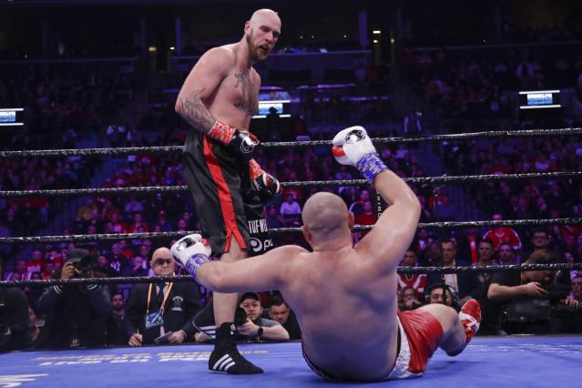 Sweden's Robert Helenius, left, knocks down Poland's Adam Kownacki during the fourth round of a heavyweight boxing match Saturday, March 7, 2020, in New York. Helenius stopped Kownacki in the fourth round. (AP Photo/Frank Franklin II)