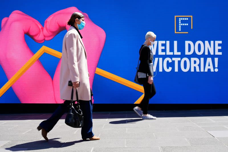 People walk past a 'Well Done Victoria' sign after coronavirus disease restrictions were eased in Melbourne