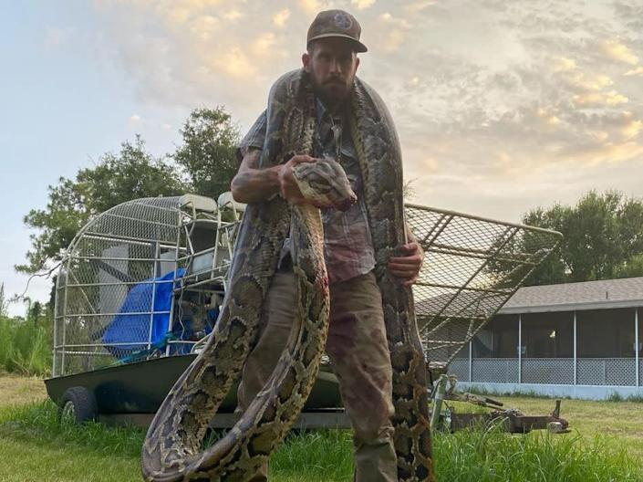Mike Kimmel with the 17 foot long snake: (Martin County Trapping & Wildlife Rescue - Facebook)