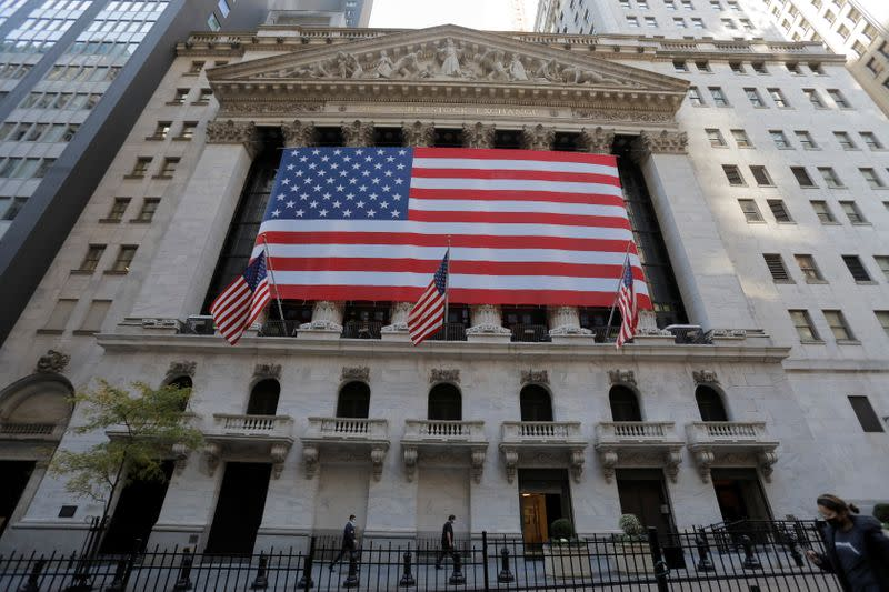People walk by a U.S. flag on the New York Stock Exchange (NYSE) following Election Day in Manhattan, New York City