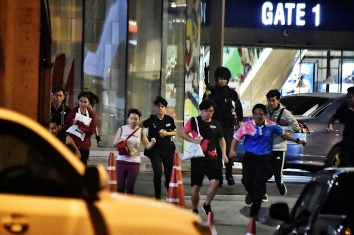Rescued by Thai commandos, people run from the shopping mall in Nakhon Ratchasima city (AFP Photo/Lillian SUWANRUMPHA )