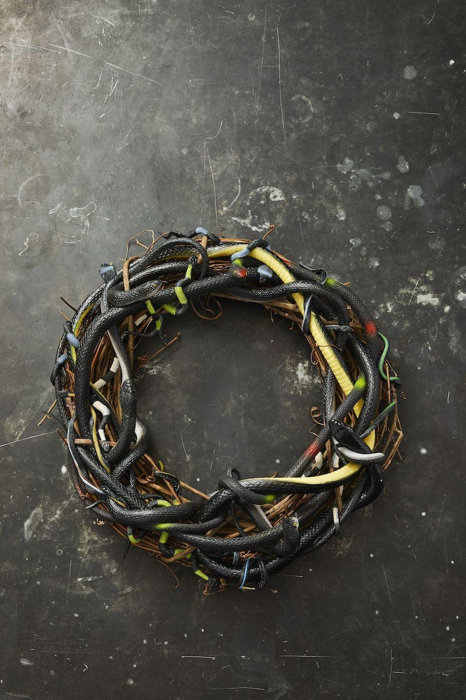 <p>Give the trick-or-treaters the heebie-jeebies with the slithery fake snake wreath.<strong><br></strong></p><p><strong>To make:</strong> Attach rubber snakes to a grapevine wreath with hot glue, weaving them in and out of each other.</p>