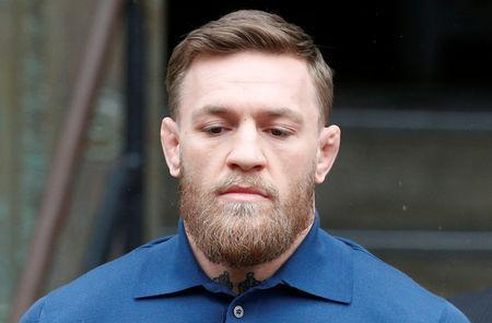 FILE PHOTO: Mixed Martial Arts fighter Conor McGregor is escorted by New York City Police (NYPD) detectives from the 78th police precinct after charges were laid against him in the Brooklyn borough of New York City, U.S., April 6, 2018. REUTERS/Brendan McDermid