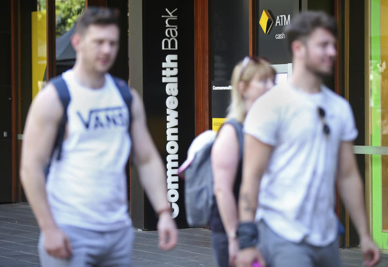 People pass by a Commonwealth Bank ATM in Sydney, Wednesday, Feb. 6, 2019. The Commonwealth Bank of Australia recorded a drop in statutory net profit in its latest half-year to 4.6 billion Australian dollars ($3.3 billion) as the nation's biggest lender was hit by costs for misconduct as well as lower profit margins and a downturn in the housing market. (AP Photo/Rick Rycroft)