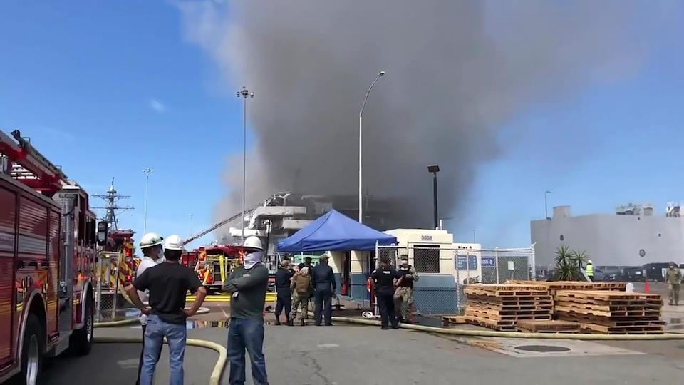 This screen grab video image obtained July 12, 2020 courtesy of the San Diego Fire Department shows fire activity aboard the US Navy ship USS Bonhomme, in San Diego, Calif. An explosion on a United States amphibious assault ship moored at a naval base in California set off a major fire and injured 18 sailors on Sunday, officials and local media said. The USS Bonhomme Richard was in port in San Diego for maintenance when the explosion and fire broke out around 9:00 am, according to the Navy Times. Scenes broadcast by CNN showed thick smoke billowing from large sections of the ship, as fireboats used water cannon to try to control the blaze.