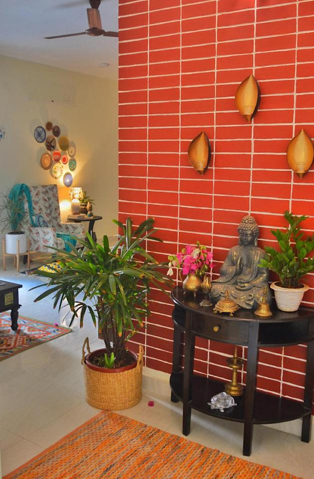 """The foyer is blissful with a statue of the Buddha, potted plants, a traditional oil lamp and wall-mounted t-light-holders. """"This space gives me lots of positive vibes,"""" says Preeti."""