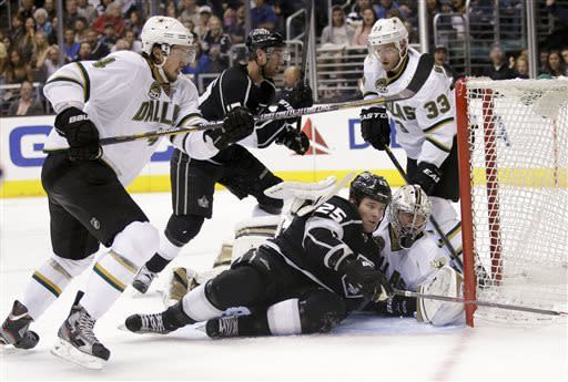 Los Angeles Kings' Dustin Penner, bottom left, and Dallas Stars goalie Kari Lehtonen, bottom right, of Finland, fall to the ice as Stars' Brenden Dillon, left, goes after the puck during the second period of an NHL hockey game in Los Angeles, Sunday, April 21, 2013. (AP Photo/Jae C. Hong)