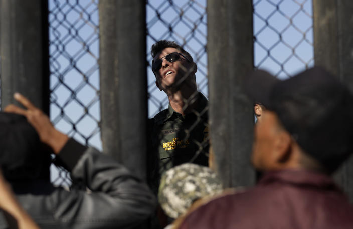 <p>A U.S. Border Patrol agent, center, looks up at the border structure as Central American migrants watch, in Tijuana, Mexico, Wednesday, Nov. 14, 2018. (Photo: Gregory Bull/AP) </p>