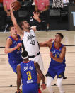 Los Angeles Clippers center Ivica Zubac (40) shoots while defended by Denver Nuggets players Nikola Jokic (15), Torrey Craig (3) and Michael Porter Jr. (1) in the first half of an NBA basketball game Wednesday, Aug. 12, 2020, in Lake Buena Vista, Fla. (Kim Klement/Pool Photo via AP)