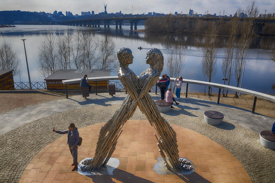 A woman takes a selfie near an art work in a city park as she enjoys a warm spring day in Kyiv, Ukraine, Tuesday, March 30, 2021. Ukraine has been under a three week coronavirus lockdown since March 20 as the country is struggling with a third wave of rising coronavirus infections. (AP Photo/Efrem lukatsky)