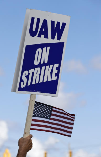 A picketer holds up a strike sign outside the the General Motors Fabrication Division, Monday, Sept. 23, 2019, in Parma, Ohio. The strike against General Motors by 49,000 United Auto Workers entered its second week Monday with progress reported in negotiations but no clear end in sight. (AP Photo/Tony Dejak)