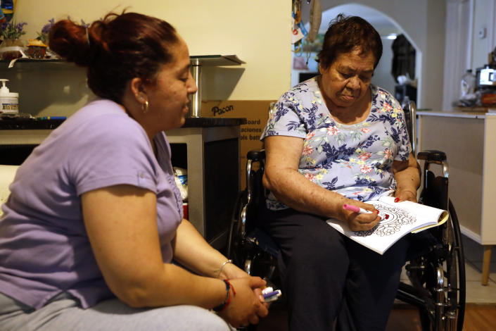 Eugenia Rodriguez, left, looks toward her 84-year-old, non-citizen mother, Francisca Perez, who colors a book, a part of her regular exercise to recover rheumatoid arthritis, Wednesday, June 30, 2021, in their house in Chicago's Little Village neighborhood. Rodriguez hasn't been eligible for insurance coverage after overstaying a visitor visa from Mexico. She used to wake up every two or three hours at night to check on her mother. Since getting health insurance through the Illinois program, her mother has all the medications she needs. (AP Photo/Shafkat Anowar)